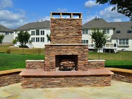 stone paved patio and outdoor stone fireplace in front of large white home
