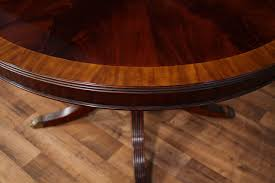 high end formal dining table with banding expands from 48 round to 66 oval to seat 6