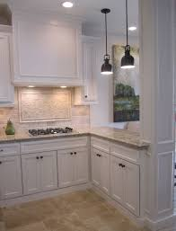 Kitchen with off white cabinets, stone backsplash and bronze accents