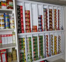 rows of diffe canned foods are d in a special shelf dispenser in a pantry