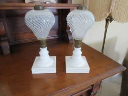 pair of antique oil lamps with milk glass base and white swirl