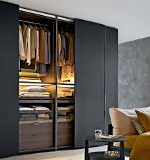 open closet with sliding doors made of black wood with clothes and blankets
