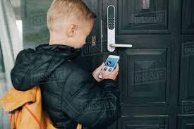 Rear view of boy using app on smart phone to unlock house door ...