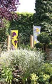 garden banners. Colourful Fabric Banners Hanging In Garden Front Of Trees And Behind Tall Grasses I