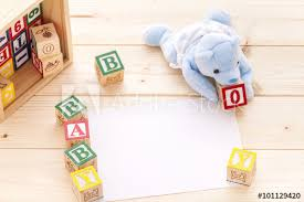 invitation with blue toy bear spelling the words baby boy with wooden a b c blocks on pinewood