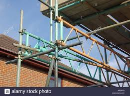 garage roof repair. scaffold erected around detached house for access to roof repair work with bridge beam units used span fragile garage