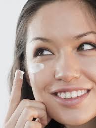 woman applying cream under her eyes