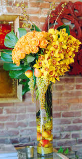 Love the fruit in the vase. Beautiful exotic arrangement with florals and  fruit
