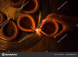 hand lighting. Happy Diwali - Hand Holding Or Lighting Arranging Diya Clay Lamp In Brass