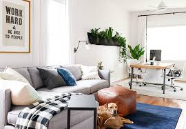 blue area rug light gray linen fiber sectional sofa with pillows white fan ceiling lamp oak laminate hardwood flooring brown leather ottoman black and white