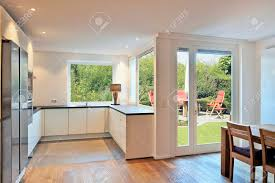 Modern Kitchen In Renovated House With View On Dining Table With