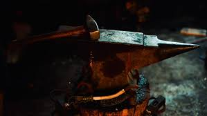 blacksmith forge sword. blacksmith clean off dross from red-hot iron and forge sword blank on anvil top o
