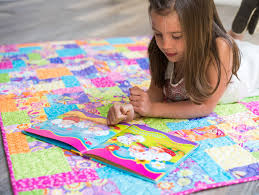 Tips for Quilting With Kids from Craftsy! & Child on Colorful Quilt Reading a Picture Book Adamdwight.com