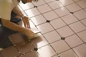 man installing tile on concrete floor