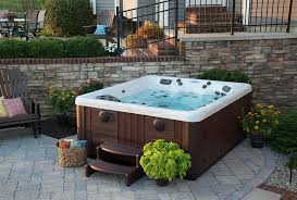 this outdoor hot tub is placed on the lower level of a backyard patio adjacent to a brick wall and bordered by potted flowers a hot tub installation on an