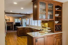 Recesed Light In White Ceiling Has Brown Cabinetry With Wooden Laminte  Flooring Also White Granite Countertop ...