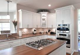 a wooden butcherblock countertop finished with a dark brown stain in a kitchen with white cabinets