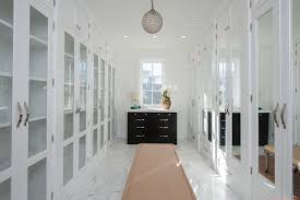 walk in closet with white mirror doors