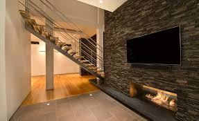 natural stacked stone veneer wall cladding on interior with tv and a fireplace