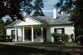 small white house with black shutters large central portico with four columns and a pediment