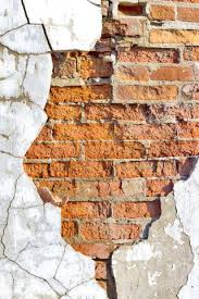 old brick wall with crumbling plaster