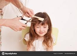 母が自宅で娘の髪をカットします ストック写真 Ekramar 155782464