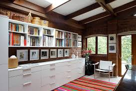 open space home office. series of open shelves and closed cabinets create ample storage space in this home office
