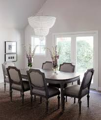 a clear beaded chandelier aerin jacqueline two tier chandelier hangs over a dark stained oval dining table lined with gray upholstered dining chairs with