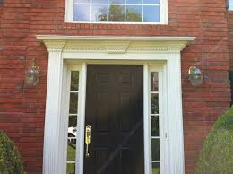 black door board with white door casing and sidelight features and gold color handle a