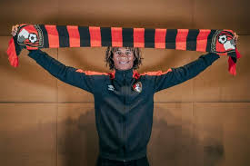 ake. nathan ake holds the bournemouth scarf after sealing his transfer (image: amy maidment/afcb/digital south)