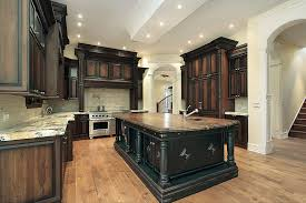 kitchen with walnut cabinets light granite counters white arches and butcher block island