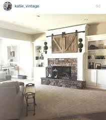 mount tv over fireplace mantle barn doors over more hanging tv brick fireplace
