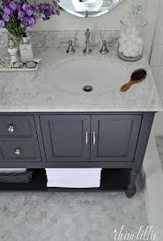 Stunning guest bath with gray bathroom vanity paired with carrara marble  countertop and subway tile backsplash. Gray bathroom cabinets with crystal