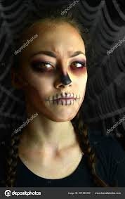 woman with halloween makeup in the background spider web