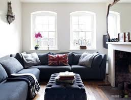 cozy gray sofa with pillows and blanket along with tufted table infront of the fireplace also big living room couches
