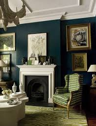 Dark teal wall color with green furniture accents. This is my dream living  room.