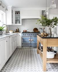 Small Wooden Island And White Cabinets Also Patterned Tiles Floor