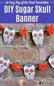 a diy sugar skull banner with free printable hanging on a brick wall