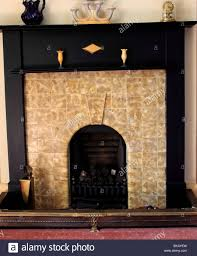 stock photo art deco fireplace with wooden surround and period ceramics