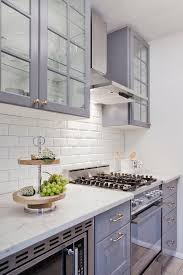stunning ikea kitchen boasts gray glass front upper cabinets and gray lower cabinets paired with honed white marble countertops and a white beveled subway