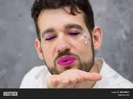 a man with make up sends an air kiss the looks like woman he has eye