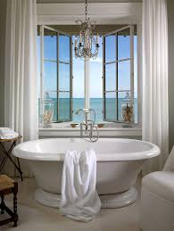 vintage freestanding bathtub next to the window with sea view in a beautiful beach style bathroom