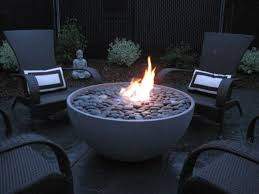 solus hemi 36 fire pit lit surrounded by seating and buddha statue