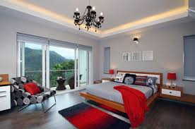 bed on wood deck also chandelier on white painted ceiling