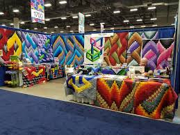 AQS QuiltWeek, Des Moines, IA | Dragonfly Quilts Blog & Here I am at the entrance of the exhibit hall in the Iowa Events Center.  The other picture shows a particularly colorful booth hosted by Fabric  Therapy, ... Adamdwight.com