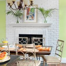L Tropical Green Dining Room Features Painted Brick Fireplace