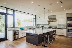 Modern Kitchen With White Lacquer Cabinets, Dark Wood Island And Light Wood  Flooring