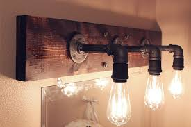 amazing vintage style bathroom lighting with 3 vintage lamps connected with iron paved with a rustic wooden plank placed on the wall and a mirror underneath