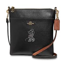 brown pebble leather coach tag golden metal coach logo on front goldtone hardware coordinates with the minnie mouse wristlet by coach sold separately