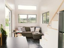 living room that leaves room to stretch your legs and a storage staircase that leads to a lofted bed french doors and plenty of windows allow light to